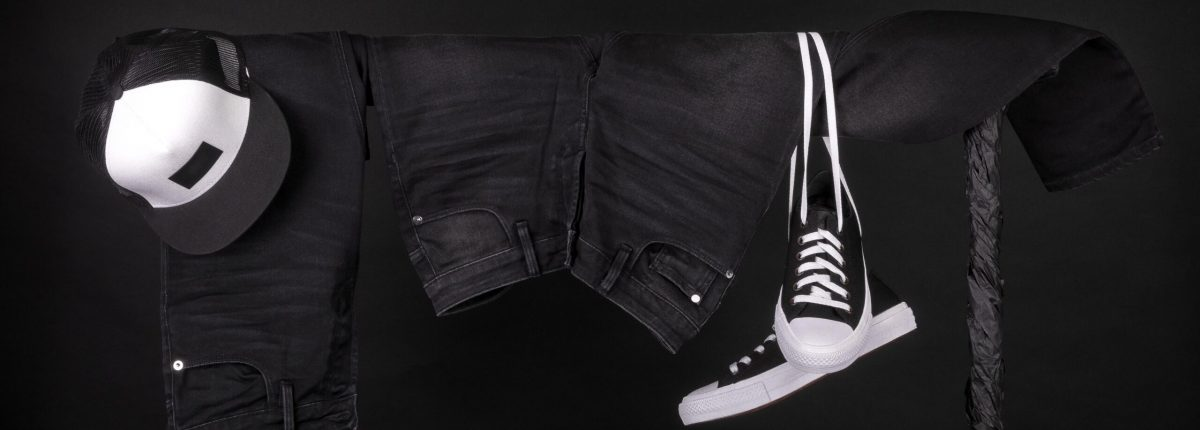 Hanging clothing. Black and white sneakers, cap and jeans on clothes rack on black background. Copy space.